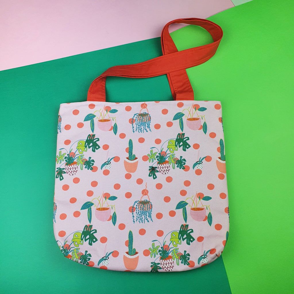 Plant lovers tote bag made from pink and green fabric with a red handle