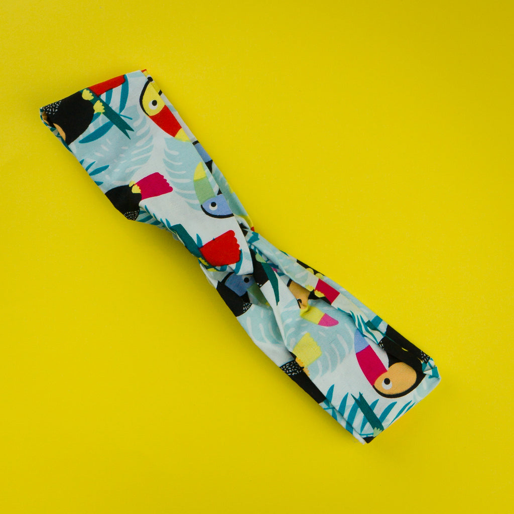 Headbands Australia for ladies fashion.  Toucan print with blue background and monstera plant leaves.
