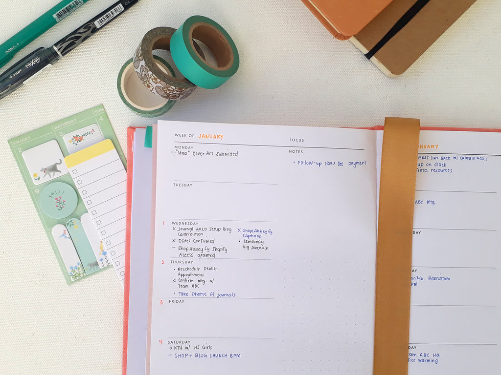 Image: a look into Nikki's weekly overview, surrounded by pens, washi tapes, and sticky notes