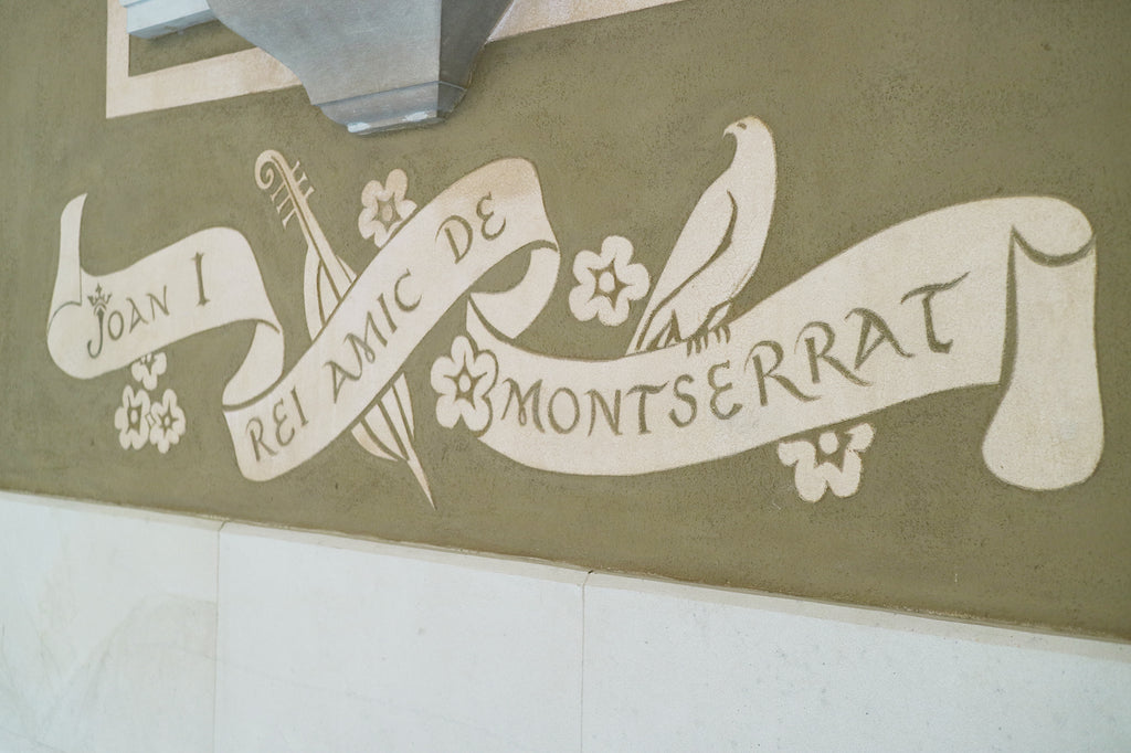 Hand-painted banner underneath the arch statue of Joan Rei de Montserrat in the Montserrat Monastery, Spain