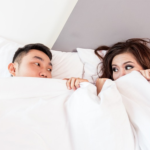 Couple Looking at Each Other In Bed Under Covers
