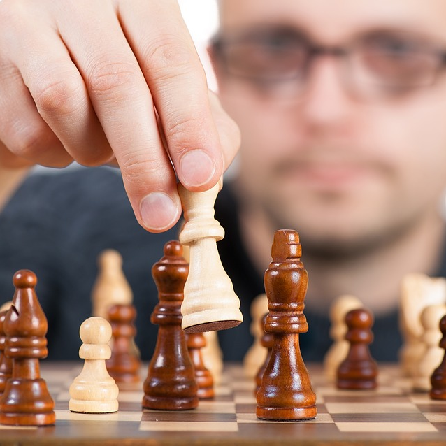 Man Placing Piece Playing Chess Thinking