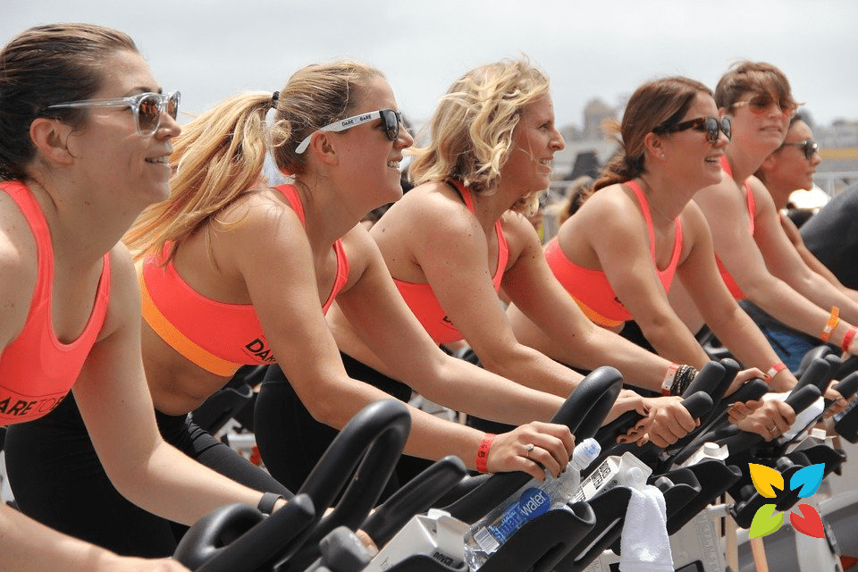Women Cycling Outdoors Stationary Bike Spin Class