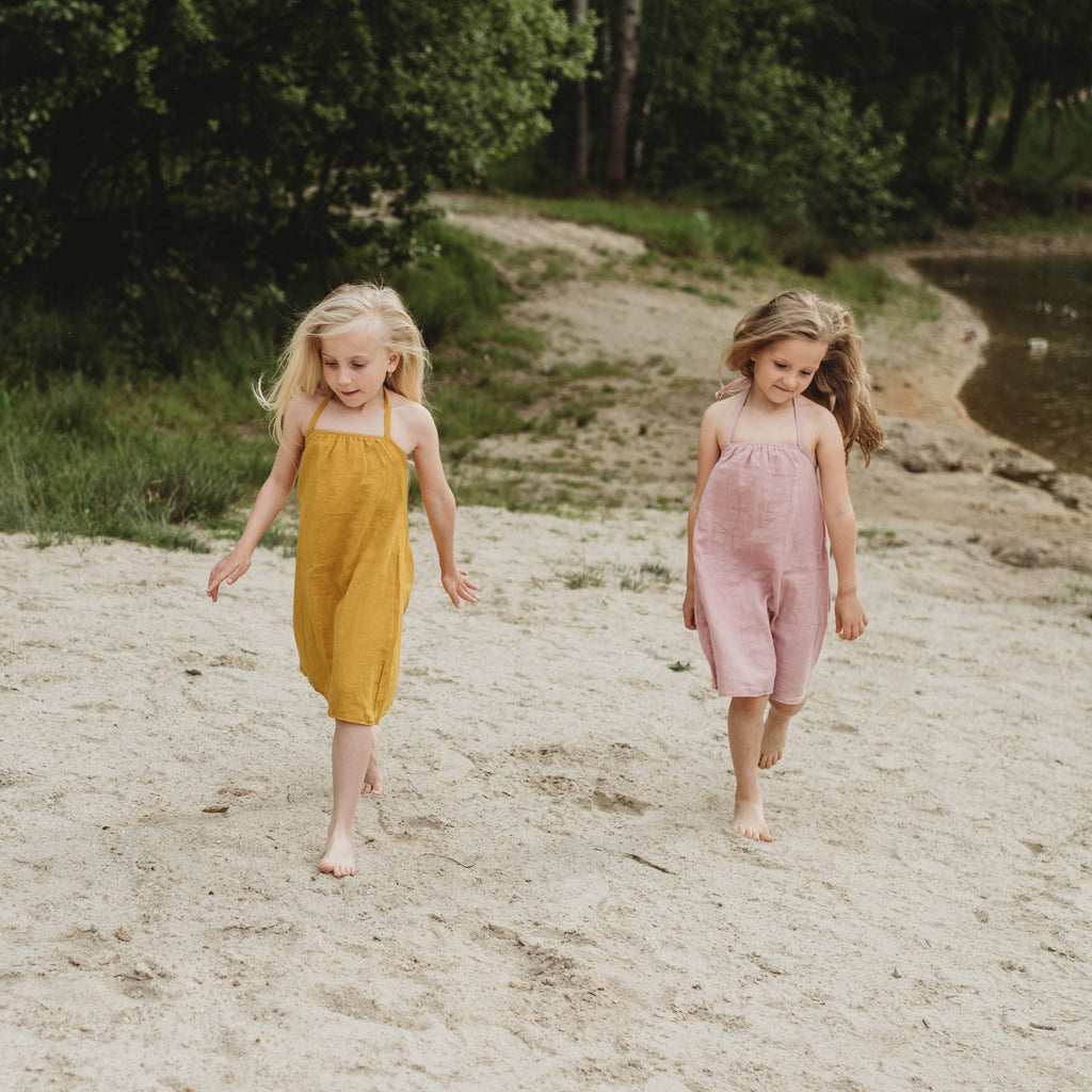 Two girls walking on a beach wearing organic muslin dresses in mustard and pink