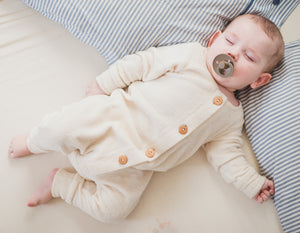 Sleeping baby boy wearing an organic cotton terry long sleeve overall with wooden buttons in vanilla - creamy white colour