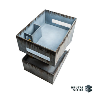 Interior view of brutalist wargaming terrain showing stairwell and 28mm miniature for scale.