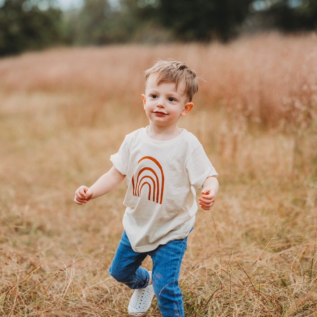 cute toddler boy running with rainbow clothes and jeans