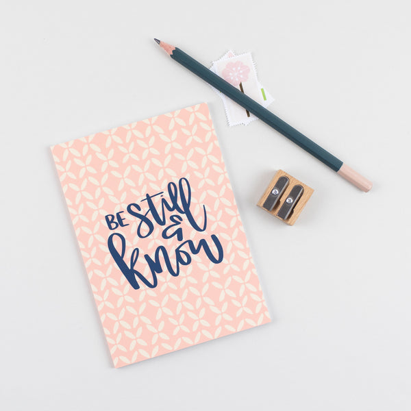 A6 mini devotional notebook be still and know hand lettered on peach colour with a hand drawn flower repeated illustration