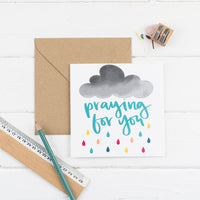 Praying for you square greeting card hand-lettered in teal amongst a cloud that is raining rainbow rain with kraft envelope