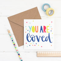 Brightly coloured hand lettered you are loved square greeting card with hand drawn triangle confetti illustration