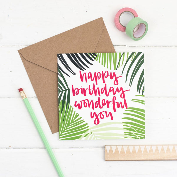 Happy birthday wonderful you raspberry lettering and a hand drawn palm frond illustration square card with kraft envelope