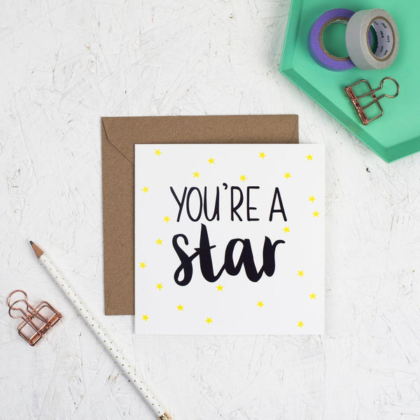You're a star hand lettered square greeting card with black lettering and illustrated yellow stars