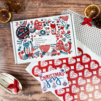 Red & green Scandinavian design festive postal gift box, red heart shaped sticker and Christmas joy gift tag