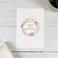 beautiful floral wreath print with the  hand lettered phrase 'yes and amen' in green, blue, pink and burgundy