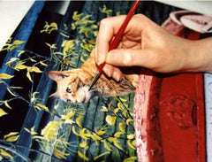 Artist's hand painting a ginger cat