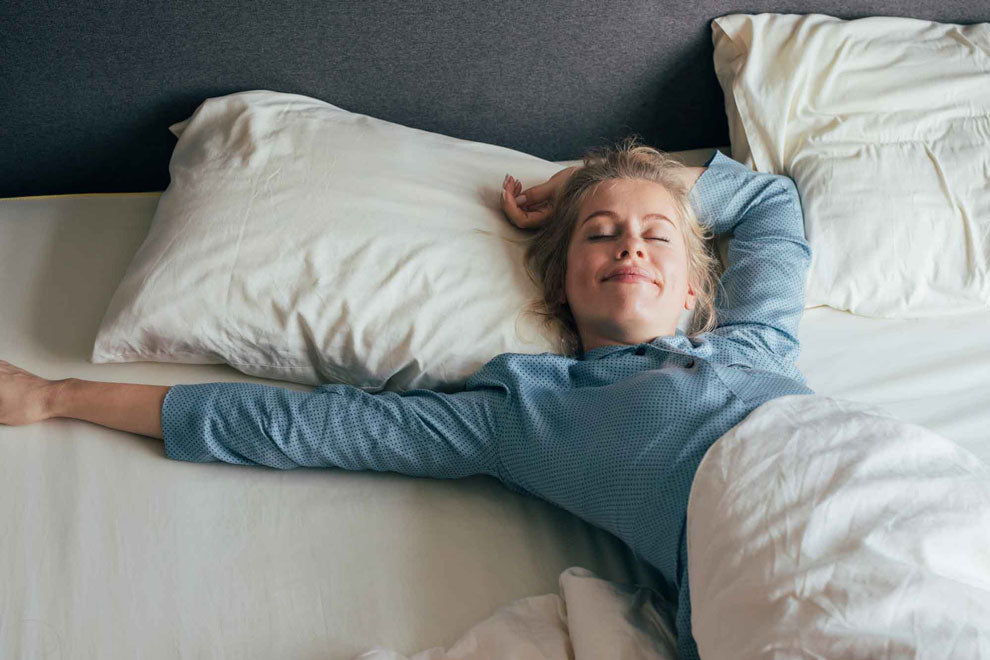 Feeling energized: happy blonde woman in pajamas stretches in bed after waking up in the morning