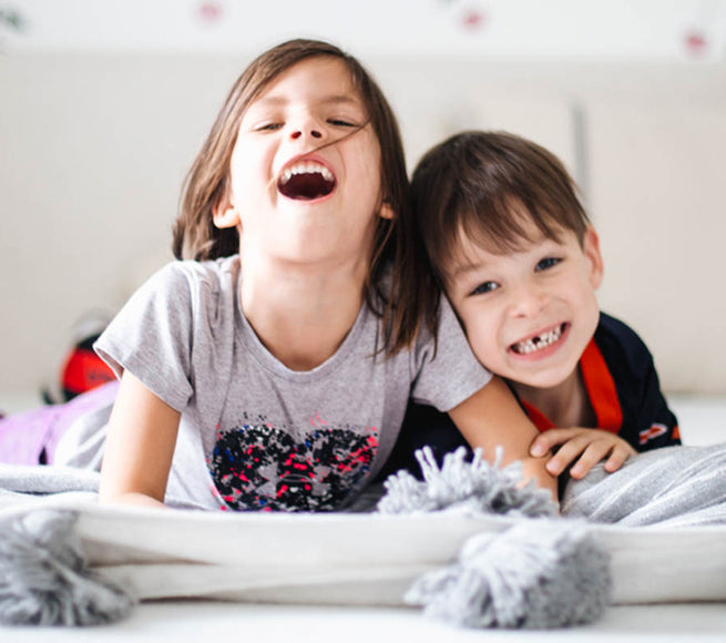 Two kids laying down on a bed and smiling