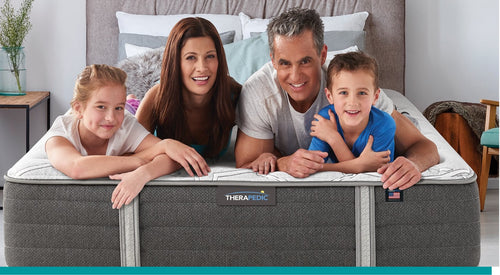 A family laying on the bed facing the foot of the bed smiling and laughing
