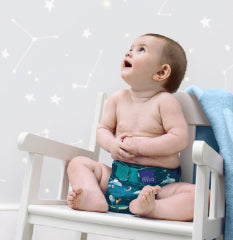 Baby looking up sitting on a chair with a star background