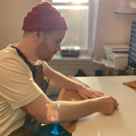 Kyle McPhee burnishing some leather by hand in his sydney workshop