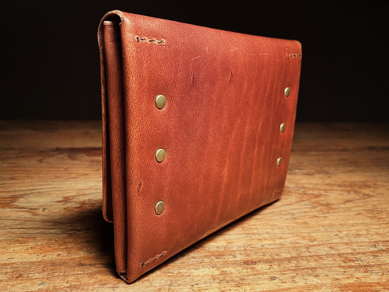 back side of fly fishing wallet in veg-tan leather with solid brass rivets