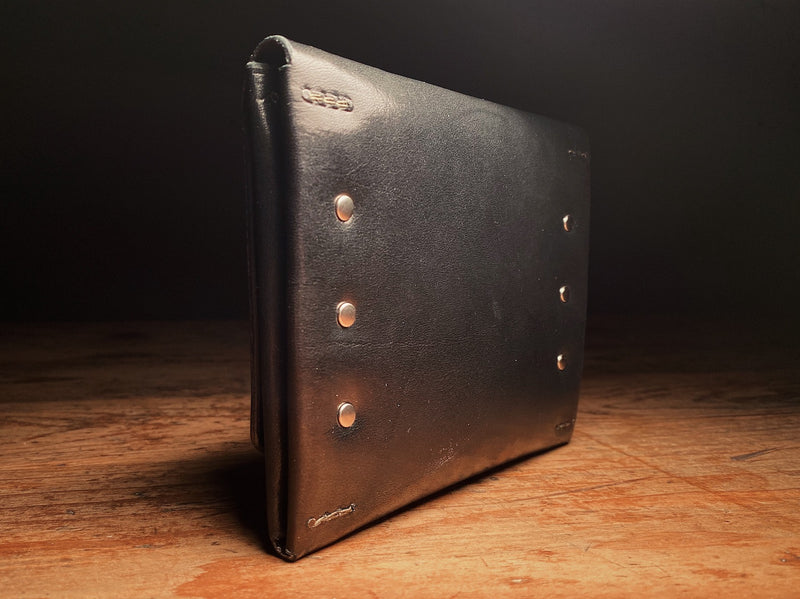 black full-grain harness leather back of the fly fishing wallet, with solid brass hardware