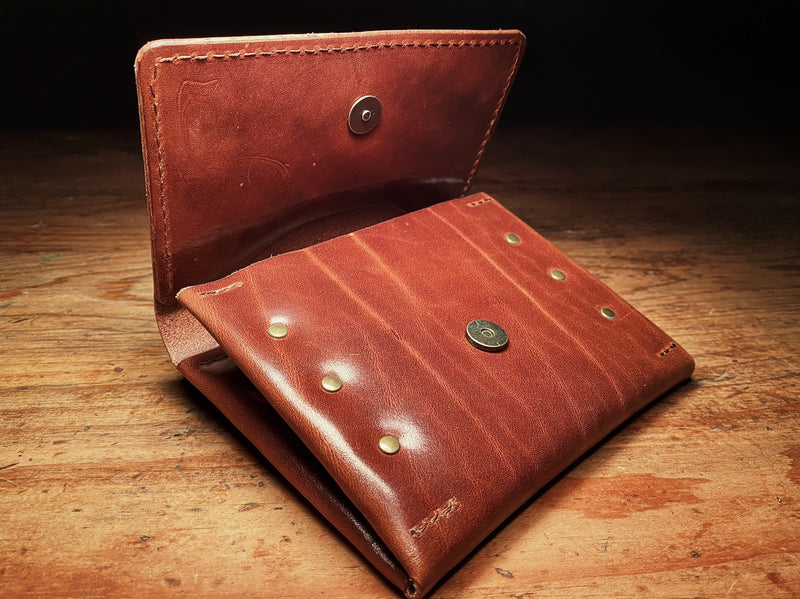 half open fly wallet, showing magnetic closure and natural markings of full-grain brown leather