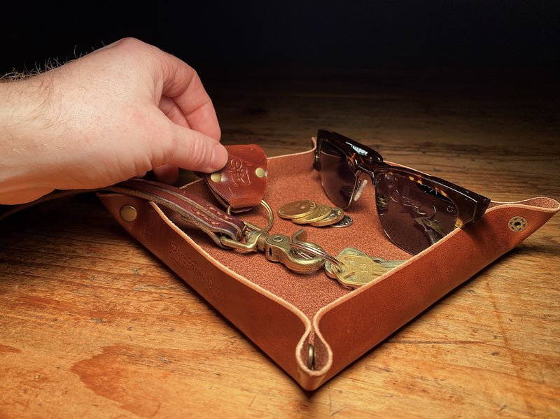 Brown veg-tan valet tray, full of small accessories and keys