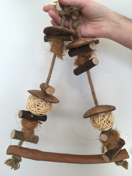 the swing has wooden pieces, coconut pieces, vine balls, and jute rope to hold it all together