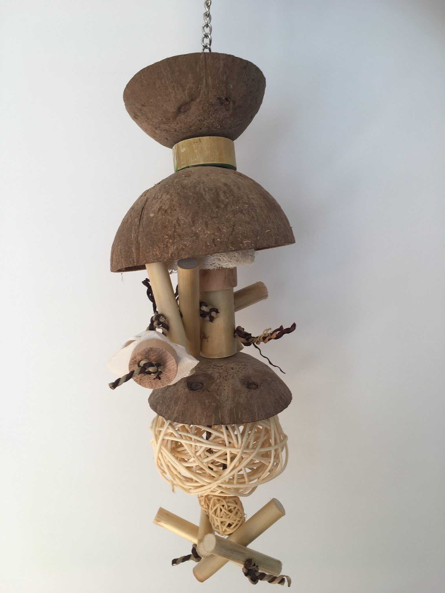 natural coconut chandelier bird toy for larger parrots, it has coconut halves, vine balls, wood, and calcium blocks