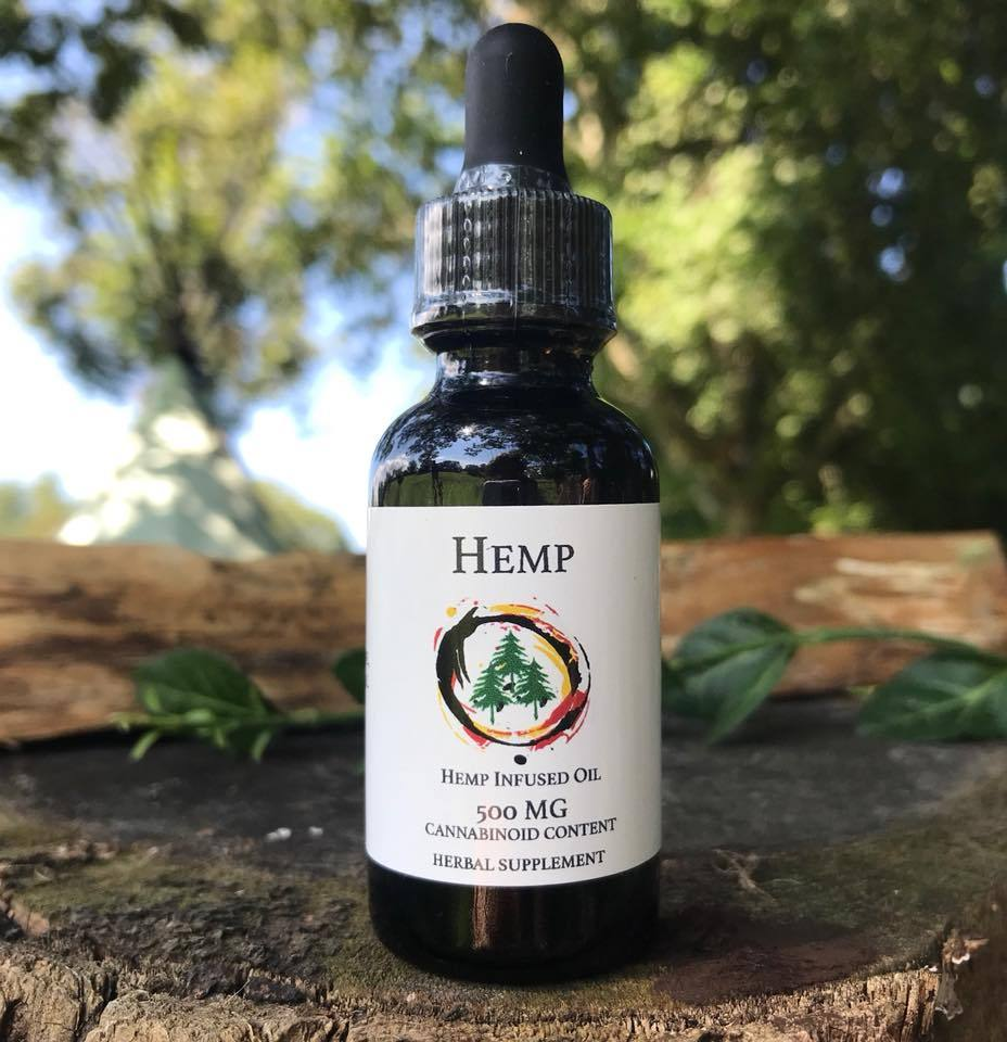 Spagyric 500mg hemp CBD extract tincture 1oz herbal supplement on a tree stump and living trees