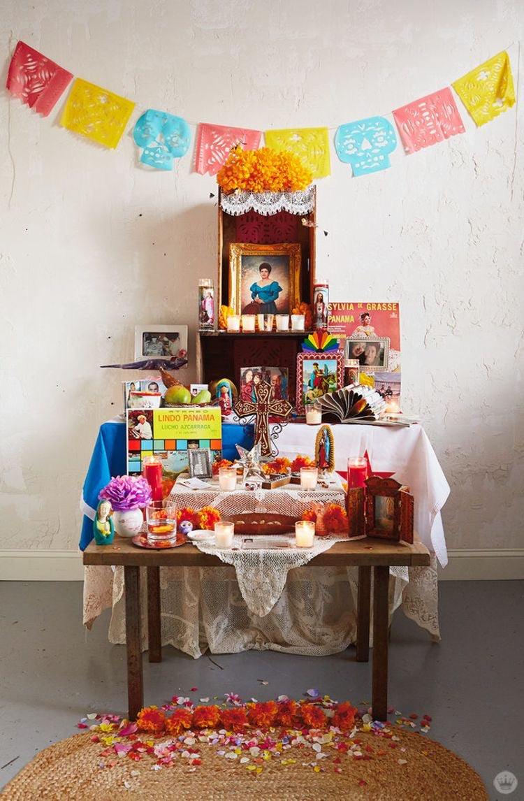 dia de los muertos alter featuring flowers, a candle, and pictures of loved ones that have passed away, placed on a table
