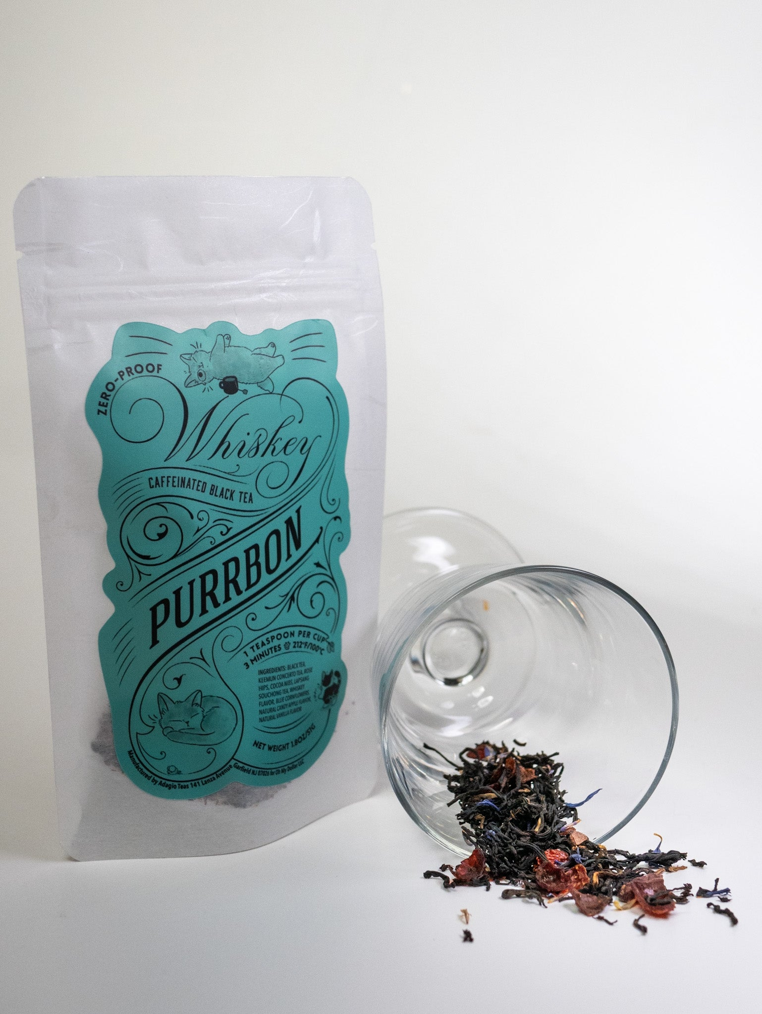 """A picture of """"purrbon"""" tea packet against a white background, with a black tea spotted with purple herbs in a glass spilling in from"""