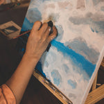 An artist paint a white and blue landscape painting on a canvas and easel.