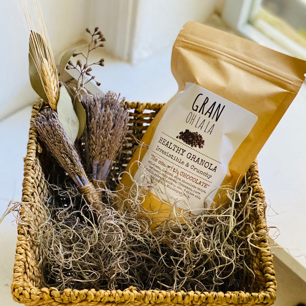 Photo of granola bag in basket with moss and dried flowers