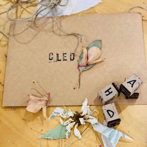 "kraft card with ""cleo"" stamp on it surrounded by stamps and dry flowers"