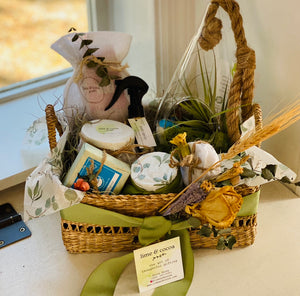 Gift baskets by window with green bow around.  Terrarium, soap, wrapped jars and moss all inside