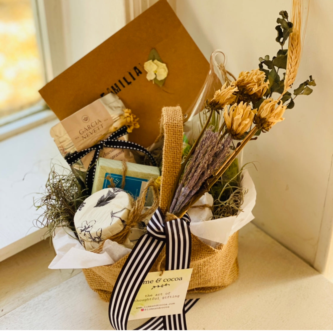 small basket with black and white ribbon by a window with dry flowers, kraft card and items inside wrapped up