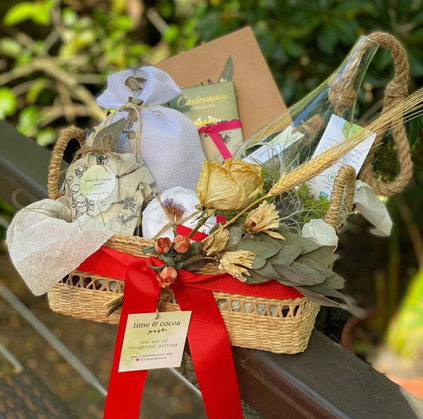 basket with red ribbon, products, terrarium, chocolate, card and dry flowers on a fence in garden