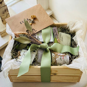 wooden crate wrapped with a green ribbon, kraft card,  jam and candle inside by a window