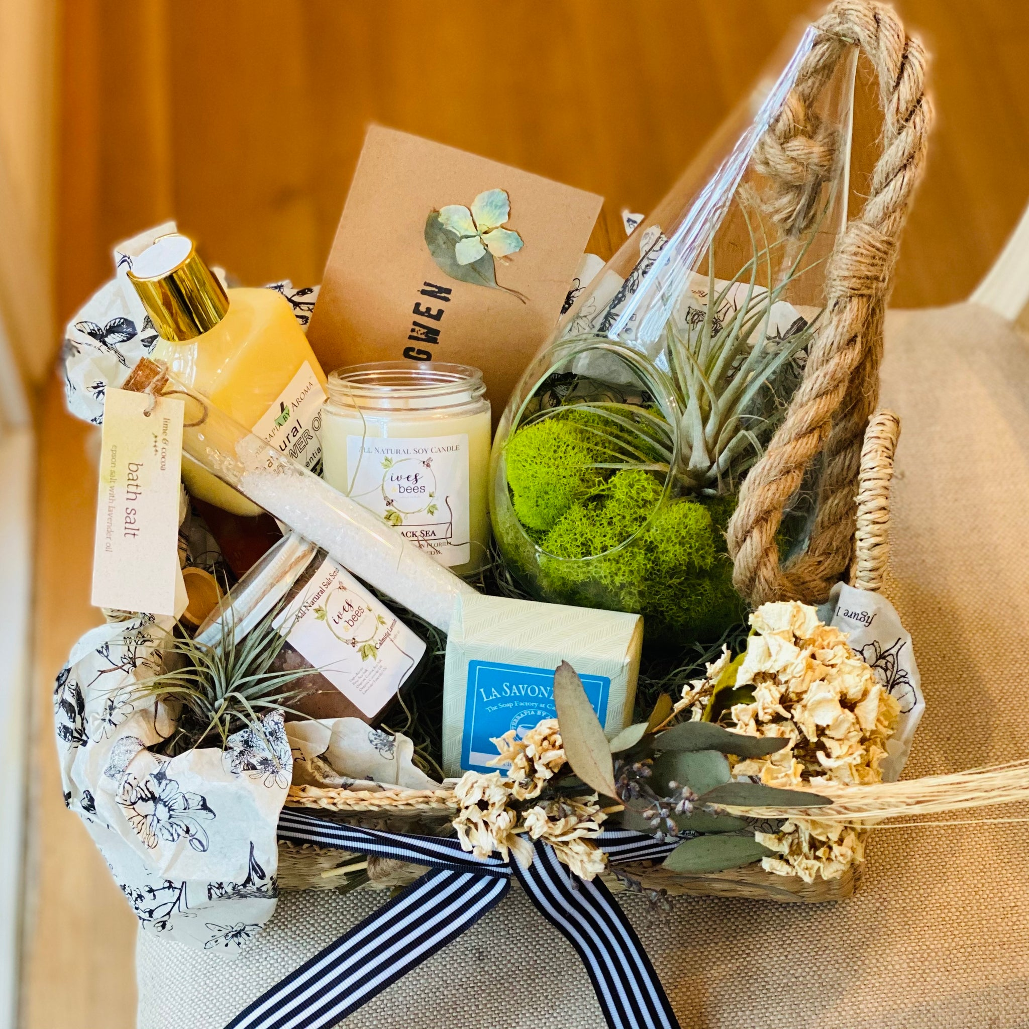 basket on a chair with air plant terrarium, shower oil, soap, candle, bath scrub and test tube with bath salt.  Card with Gwen stamped on it.