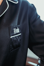 Load image into Gallery viewer, Close up of Doña Sleepwear logo on black silk sleepwear