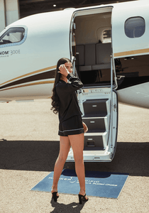 Back of model wearing black silk pyjamas in front of private jet