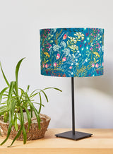 Teal fabric lampshade with vibrant wildflower print. Pink, orange, yellow and green leaves and flowers against a dark green background. Beautiful when lit