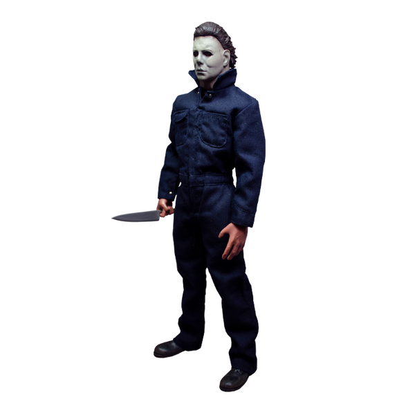 This is a Halloween 1978 Michael Myers action figure and he has a white face, brown hair, blue coveralls and he is holding a silver knife while turned to the right.