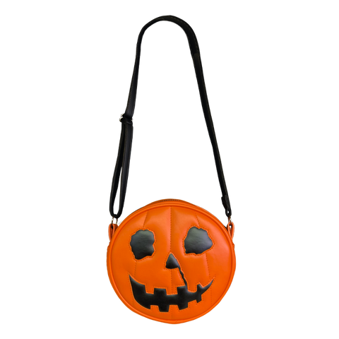 This is a Halloween 1978 pumpkin purse that is orange with a black strap and has black eyes, black nose and an orange smile.