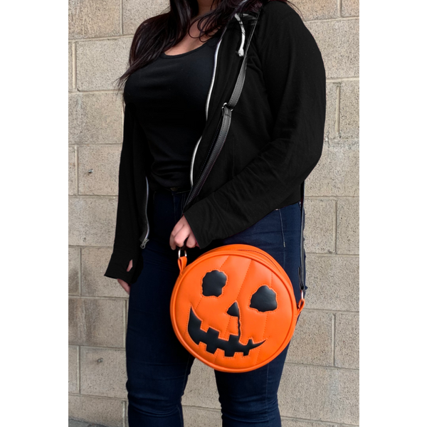 This is a Halloween 1978 pumpkin purse that is orange with a black strap and has black eyes, black nose and an orange smile. and is on someone with jeans and a black sweatshirt.