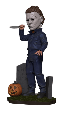 This is a 2018 Michael Myers NECA head knocker, where he is holding up a knife in his hand, has tombstones and a pumpkin around him and is wearing a white mask with brown hair and grey coveralls.