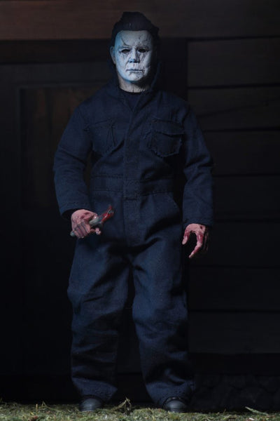 "This is a NECA 8"" clothed action figure from Halloween 2018 of Michael Myers, who is wearing a grey and weathered mask, grey coveralls, boots and is holding a knife."