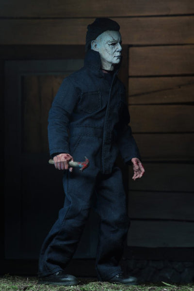 "This is a NECA 8"" clothed action figure from Halloween 2018 of Michael Myers, who is wearing a grey and weathered mask, grey coveralls and is holding a knife."